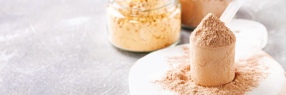 This is a scoop of synthetic protein powder with a jar of lentils.