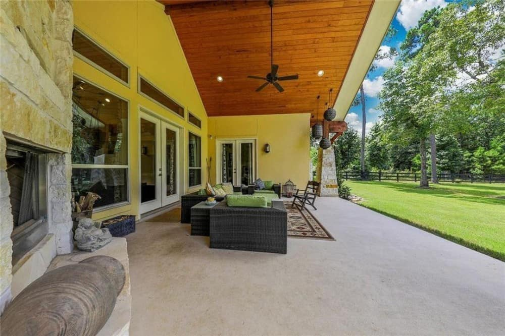 Outdoor lounge with a large stone fireplace and wicker seats over concrete flooring.