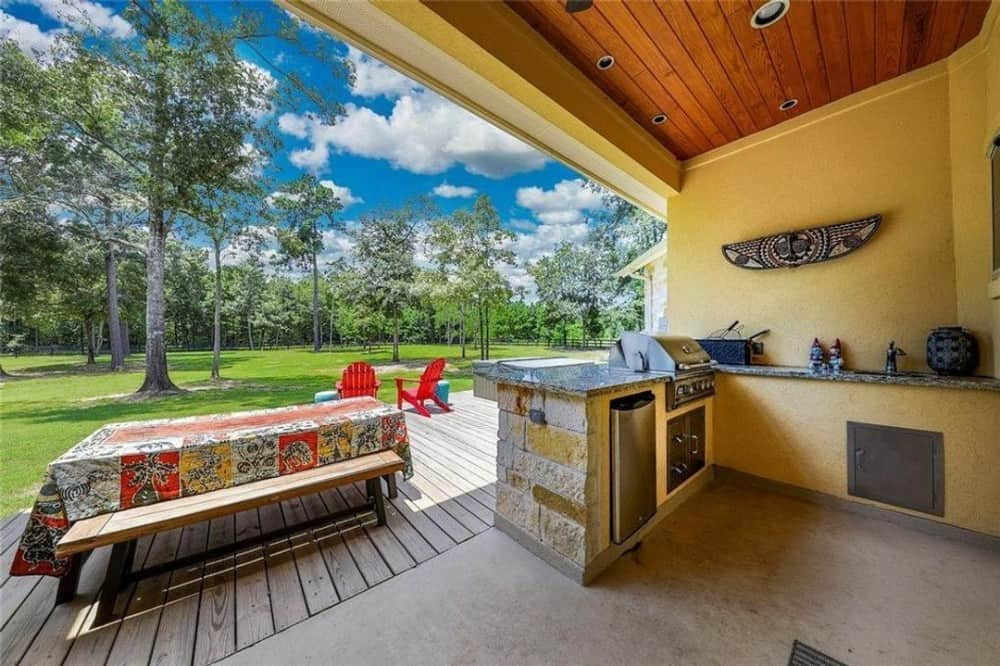 The cooking patio offers a built-in grill, eating bar, and a rectangular dining set.