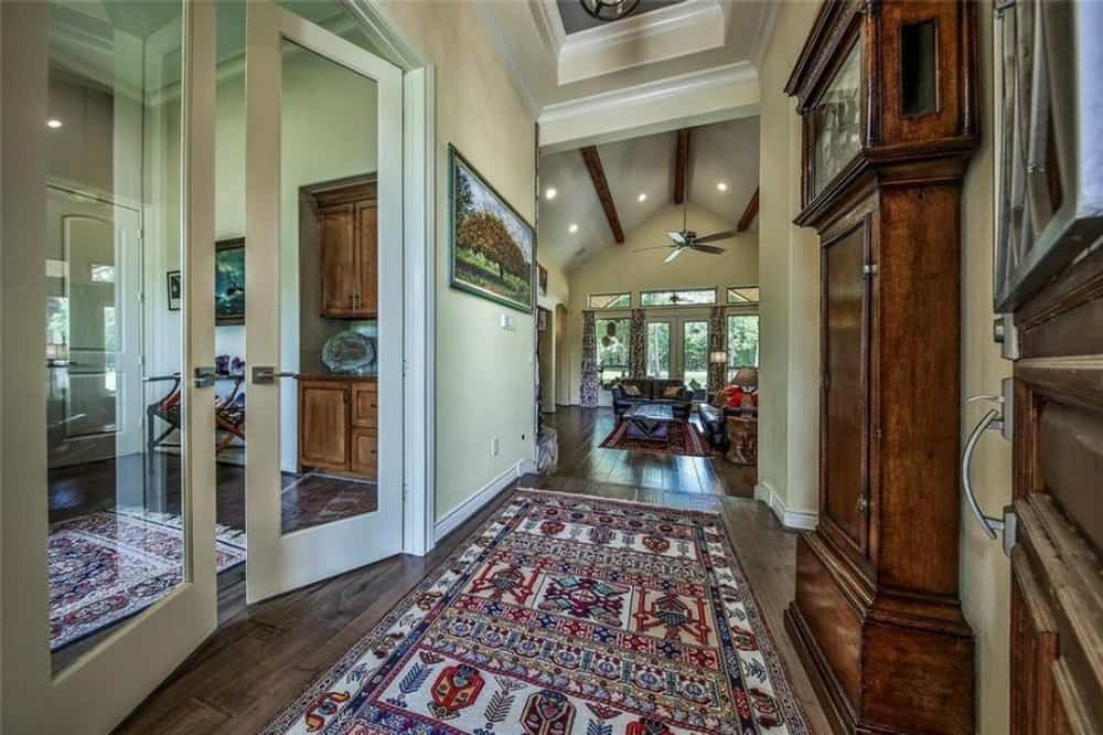 The foyer has a tribal area rug and a tray ceiling. A french door on its left opens to the study.