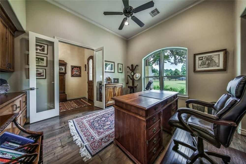Study with a wooden desk, a leather swivel chair, and a tasseled area rug under the shed ceiling mounted with a wrought iron fan.
