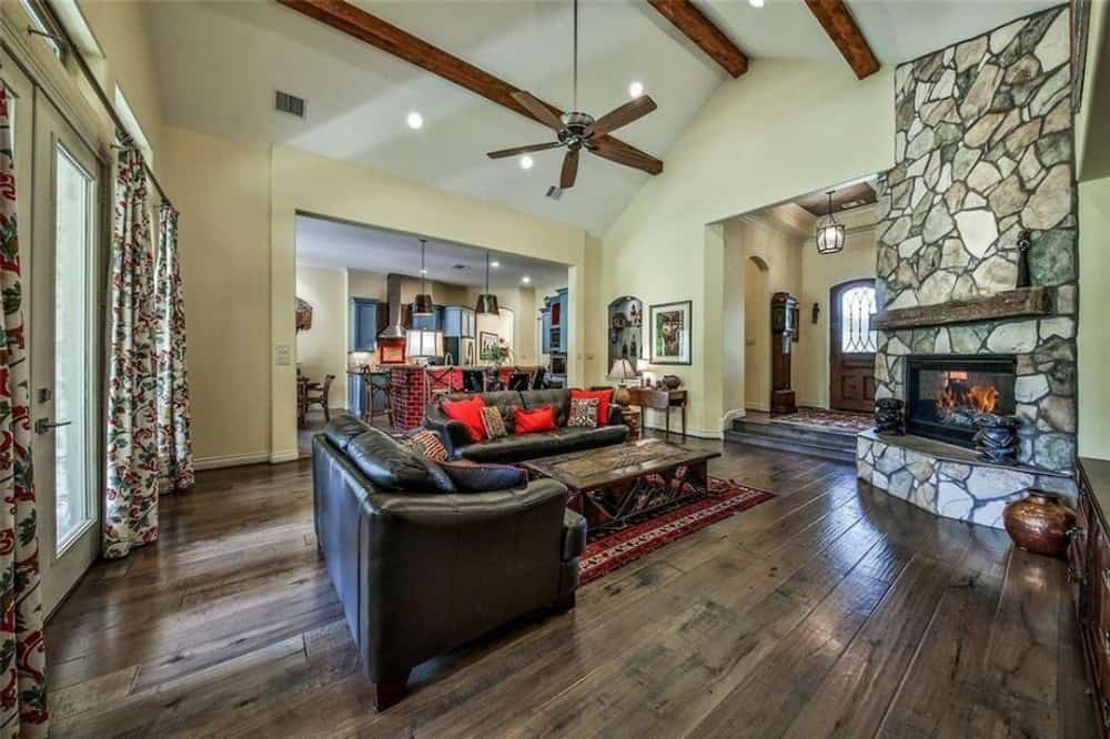 A vaulted ceiling lined with rustic wood beams crowns the family room.
