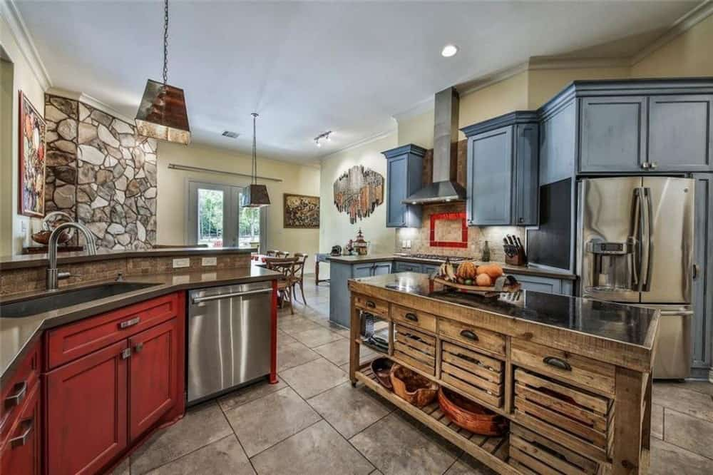 The kitchen is equipped with multicolored cabinets, stainless steel appliances, a rustic island, and a peninsula with a raised eating bar.