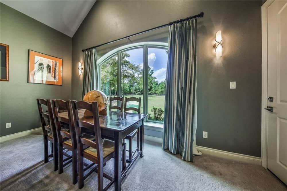 Formal dining room with a dark wood dining set, gray walls, and a large arched mirror framing the surrounding landscape.