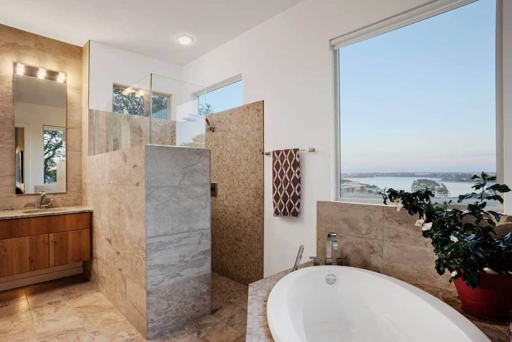 Primary bathroom with a wooden vanity, a walk-in shower, and a corner tub placed under the picture window overlooking a breathtaking view.