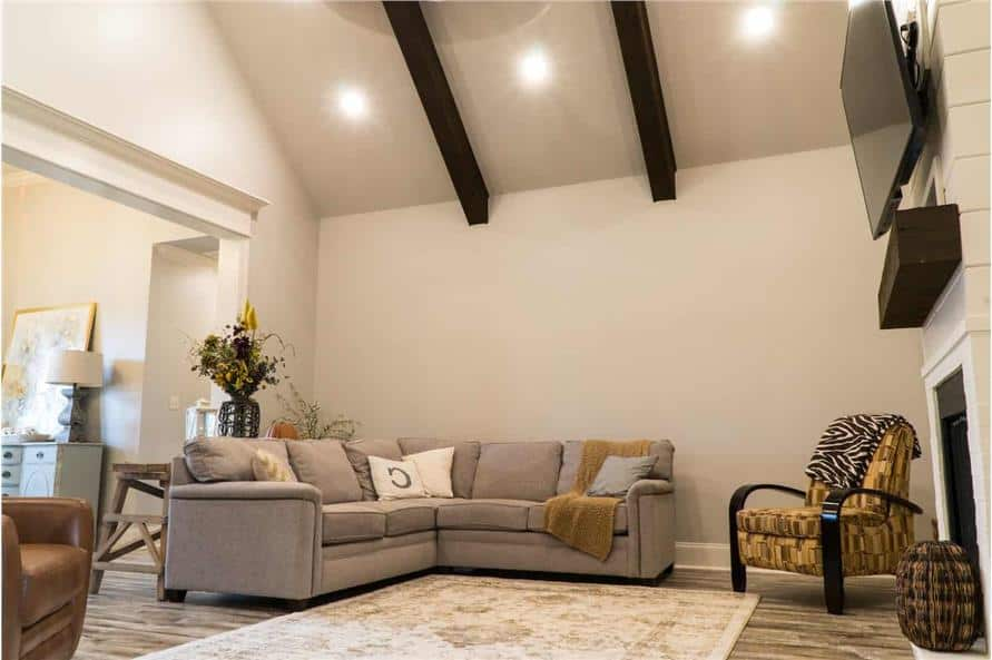 Great room with a V-shaped sofa, a patterned armchair, and a fireplace under the cathedral ceiling lined with dark wood beams.