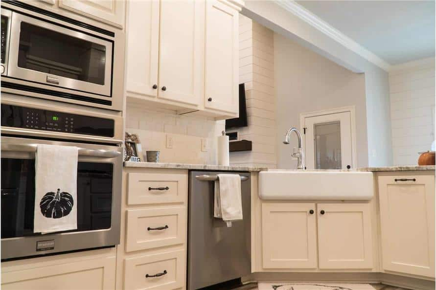 The kitchen peninsula is also fitted with a farmhouse sink paired with a gooseneck faucet.