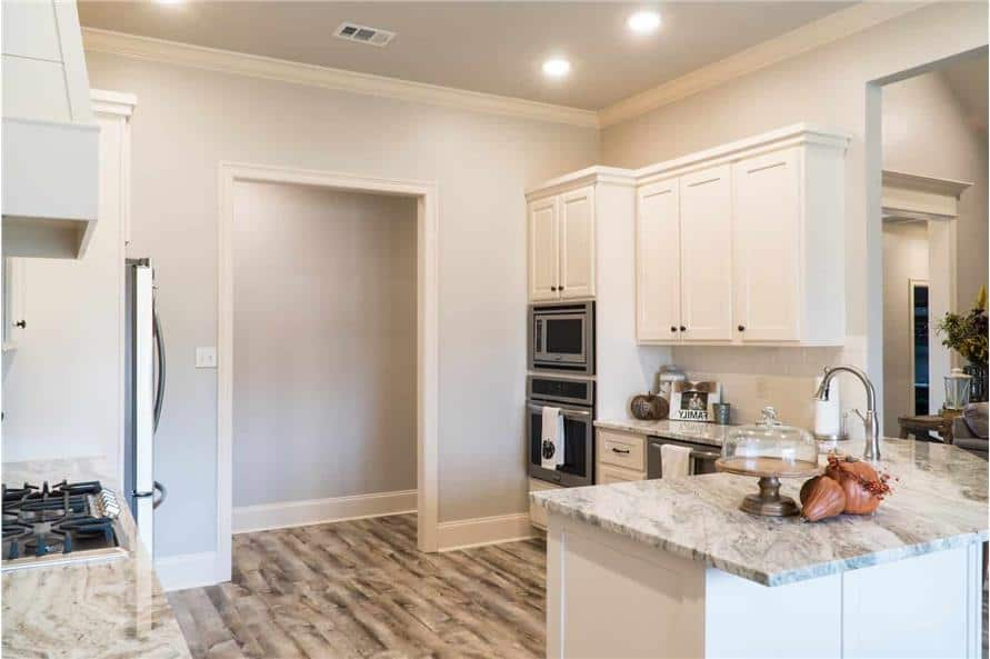 Kitchen with white cabinetry, stainless steel appliances, and a built-in cooktop.