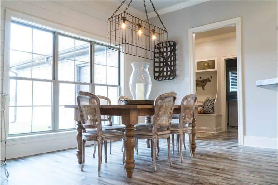 Natural light from the large window brightens the dining room. It has an industrial chandelier and a wooden dining table surrounded by distressed white chairs.