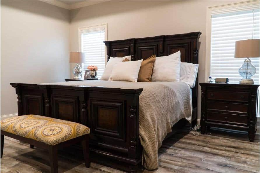 Primary bedroom with a dark wood bed, matching nightstands, and a patterned ottoman.