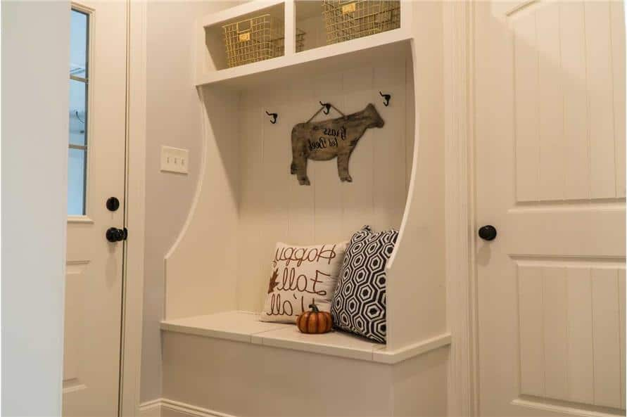 Kid's nook with a built-in storage locker filled with wire baskets and patterned pillows.