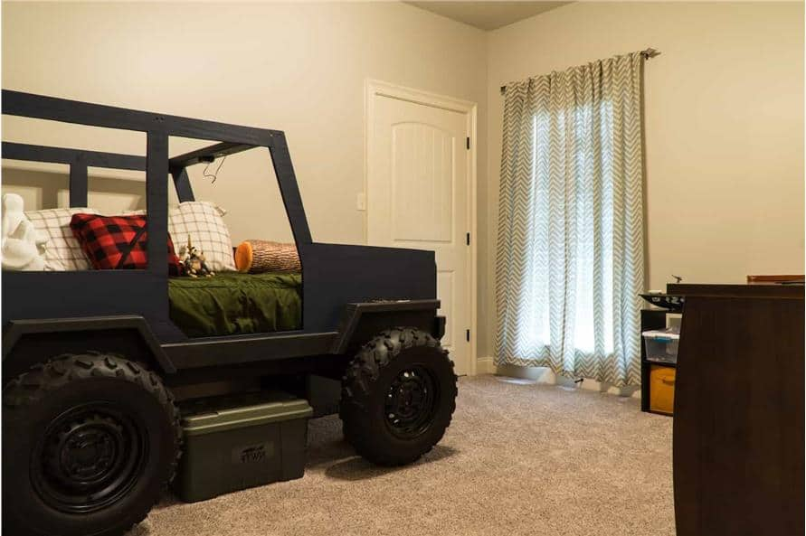 Kid's bedroom with a wooden desk and a custom vehicle bed over the carpet flooring.