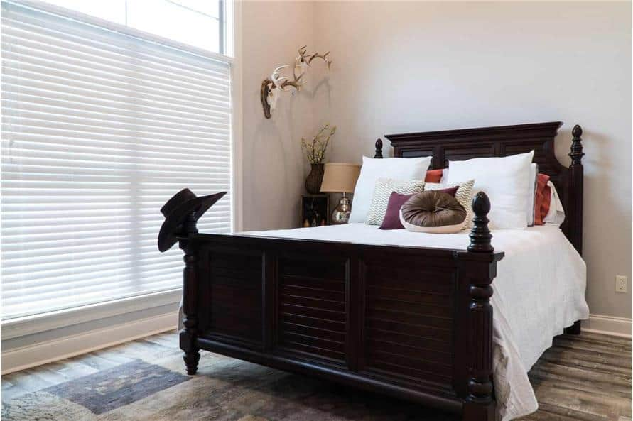 This bedroom offers a dark wood bed and a massive window bringing an abundant amount of natural light in.