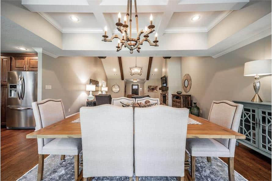 Recessed lights along with a contemporary chandelier hanging from the coffered ceiling illuminate the dining area.