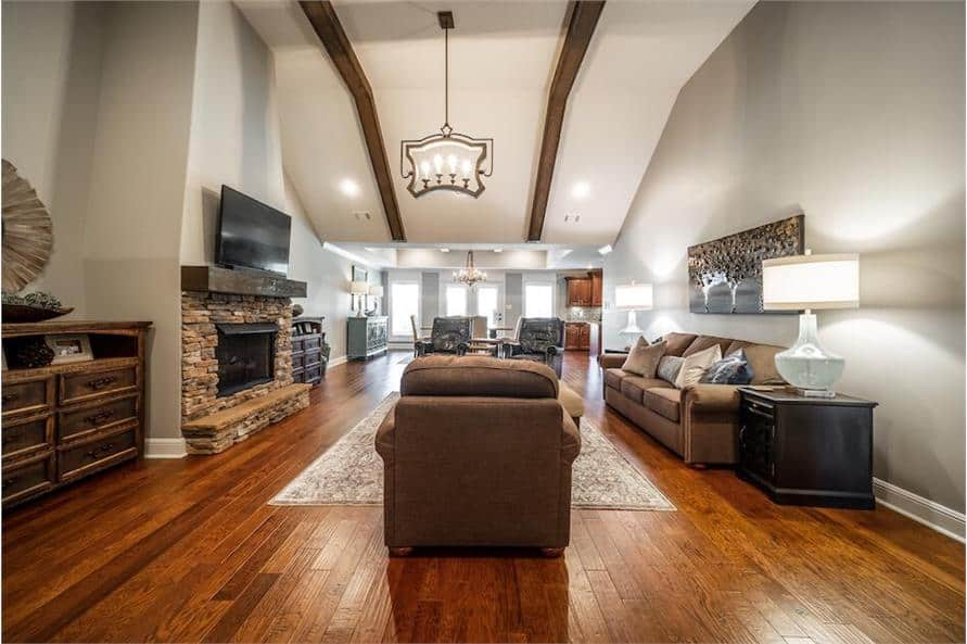 A high vaulted ceiling lined with exposed wood beams crowns the great room.
