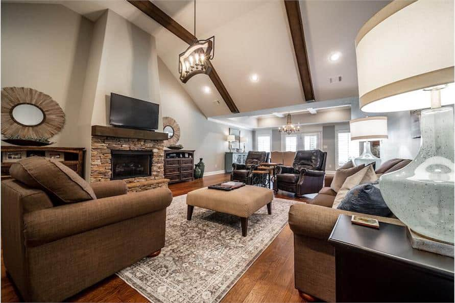 The great room offers fabric and leather upholstered seats, an ottoman, and a stone fireplace topped with a TV.