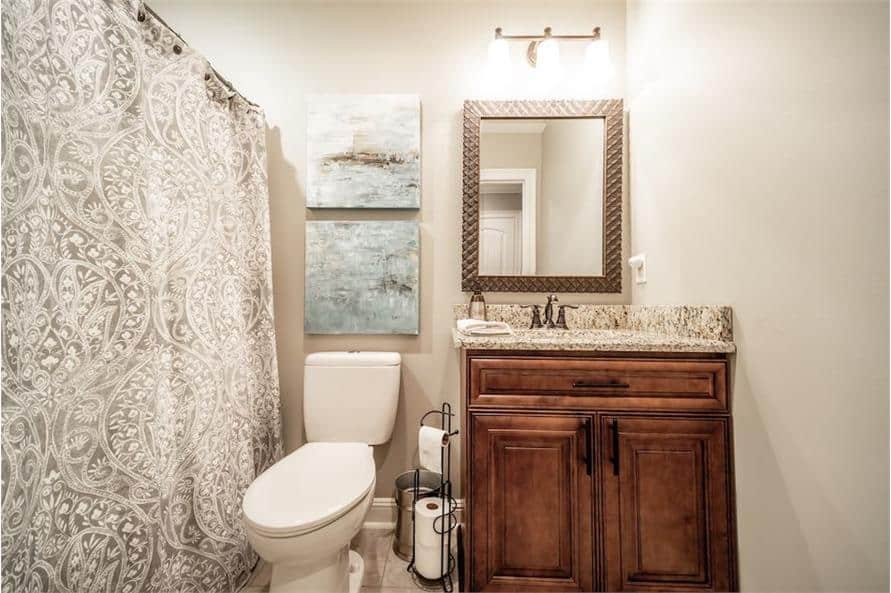 This bathroom is equipped with a wooden vanity, a toilet, and a tub and shower combo concealed behind the patterned curtain.