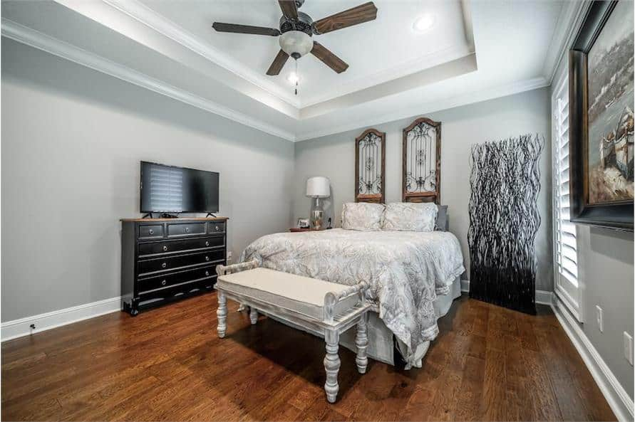 This bedroom has a tray ceiling, a dark wood dresser, and a skirted bed with a distressed bench at its end.