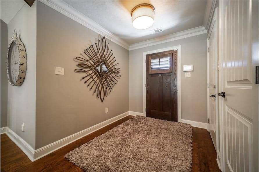 Foyer with a rustic entry door, a shaggy area rug, and a decorative mirror gracing the gray walls.