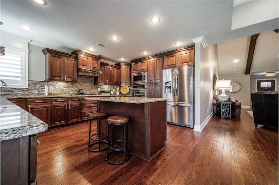 The kitchen includes stainless steel appliances and a couple of round bar stools complementing the breakfast island.
