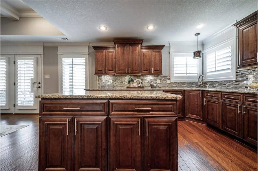 The kitchen has wooden cabinetry, granite countertops, linear tile mosaic backsplash, and a center island. Louvered windows invite natural light in.