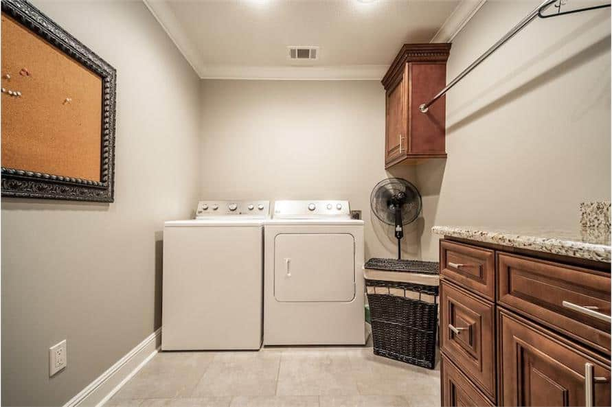 Laundry room with white appliances, a wicker hamper, wooden cabinets, and a granite counter.