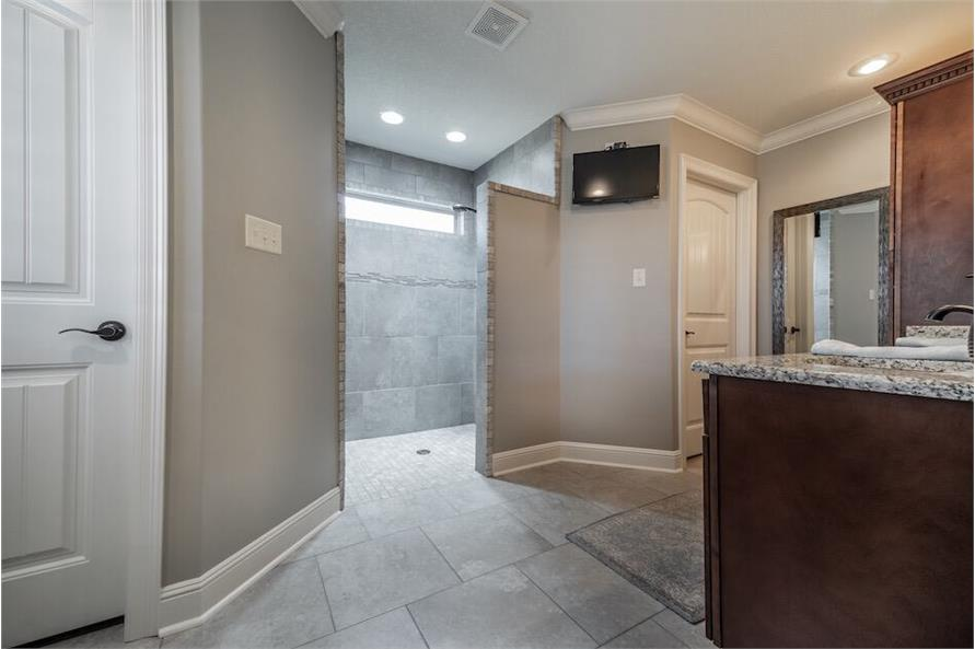 Primary bathroom with a granite top vanity, a water closet, and a walk-in shower brightened by a clerestory window.