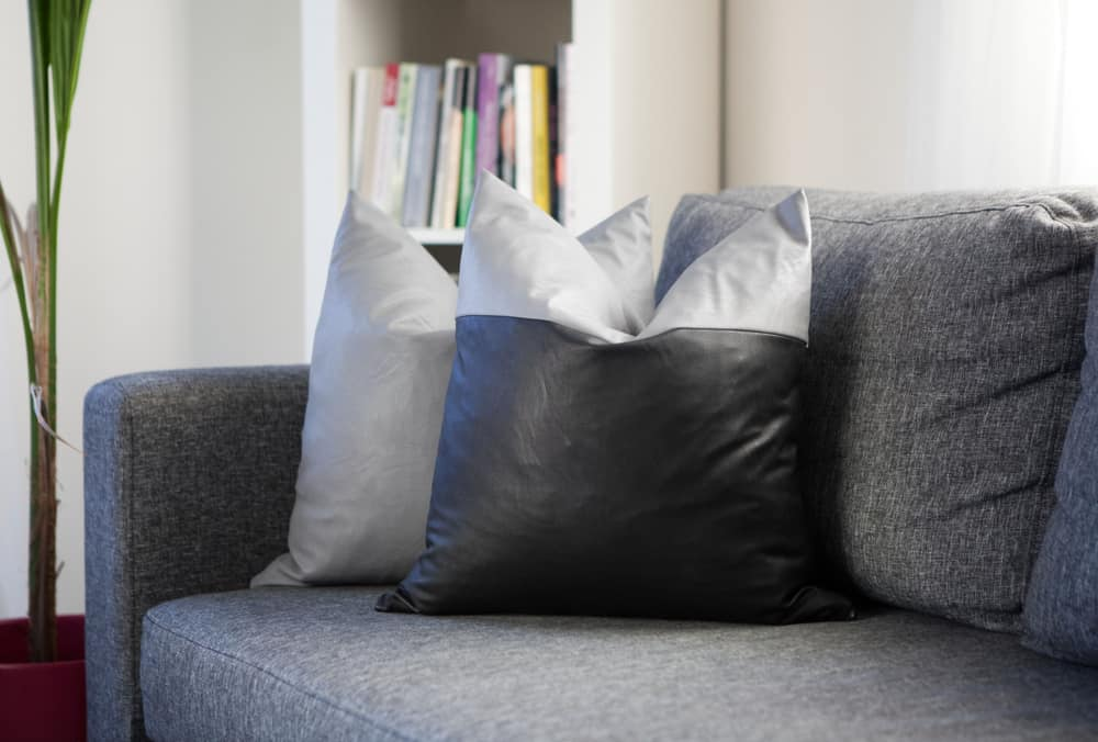 A close look at a sofa with faux leather throw pillows.