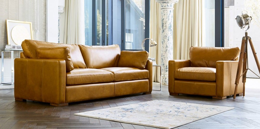 This is a sofa with brown leather upholstery to match the herringbone flooring.