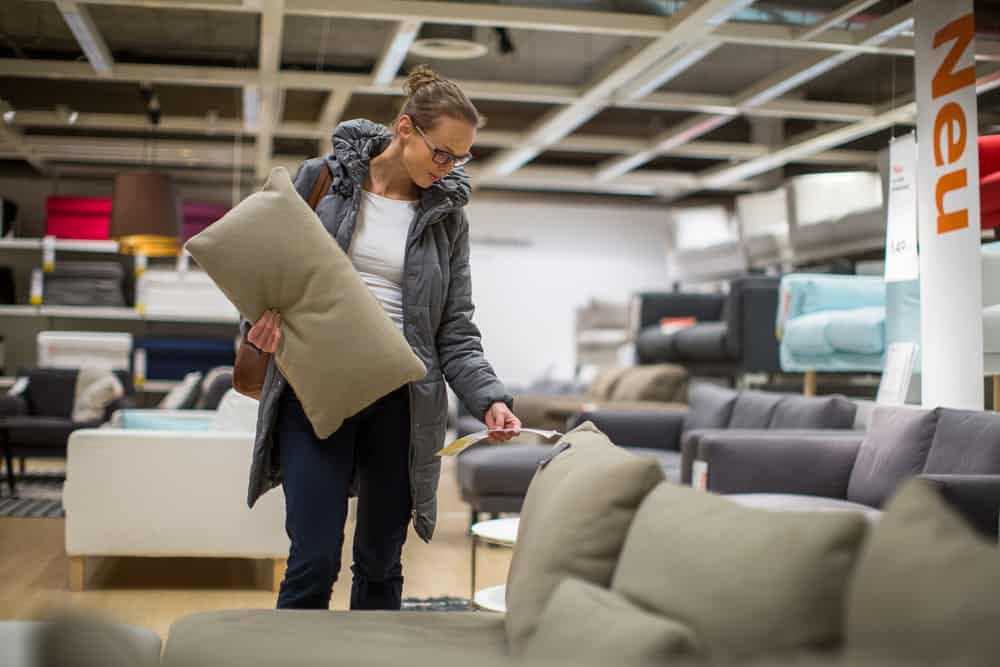 This is a close look at a woman browsing over sofas at a furniture store.