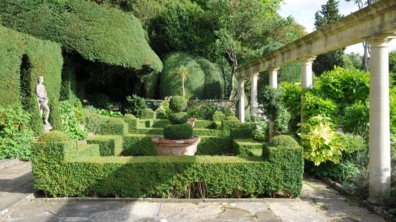 Large patio with topiary shapes bordered with pillars and containing statues