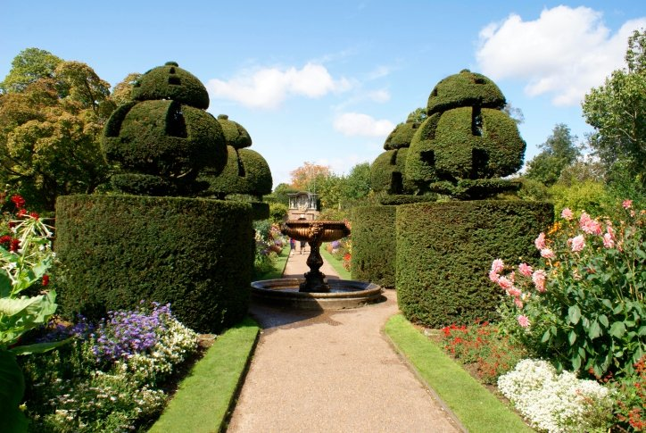 Garden with a mixture of topiary trees, flowers, fountain and walkway