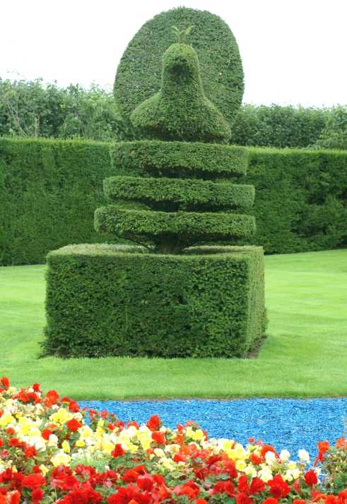 Photo of sculpted tree with large square base, then rings topped with a bell.