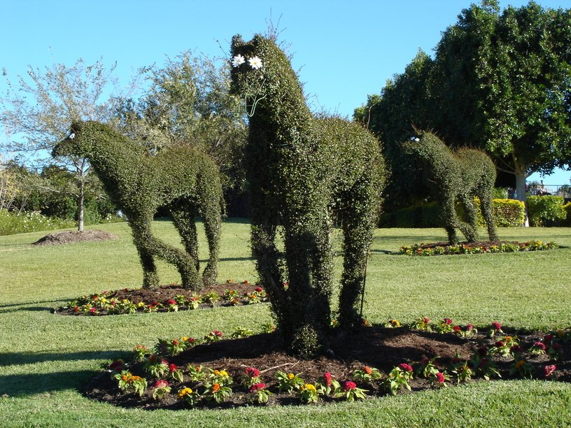 Topiary horses running in a large field with gardens
